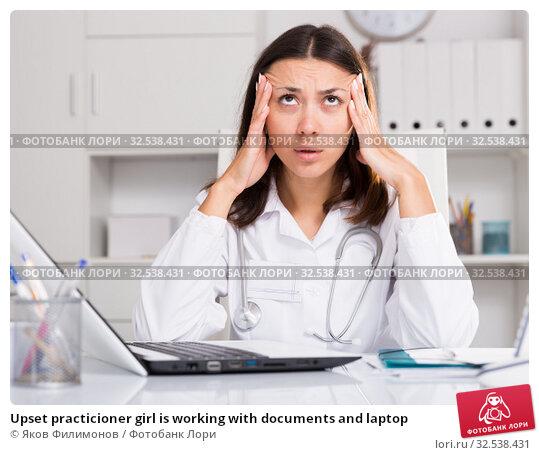 Купить «Upset practicioner girl is working with documents and laptop», фото № 32538431, снято 1 мая 2018 г. (c) Яков Филимонов / Фотобанк Лори