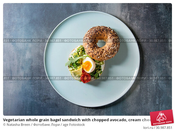 Купить «Vegetarian whole grain bagel sandwich with chopped avocado, cream cheese, sun dried tomatoes, egg, served on ceramic plate over blue texture background. Flat lay, space», фото № 30987851, снято 19 июля 2019 г. (c) age Fotostock / Фотобанк Лори