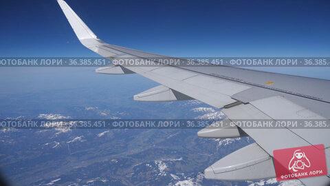 View from passenger cabin window of plane wing over Austrian Alps. Стоковое видео, видеограф Яков Филимонов / Фотобанк Лори