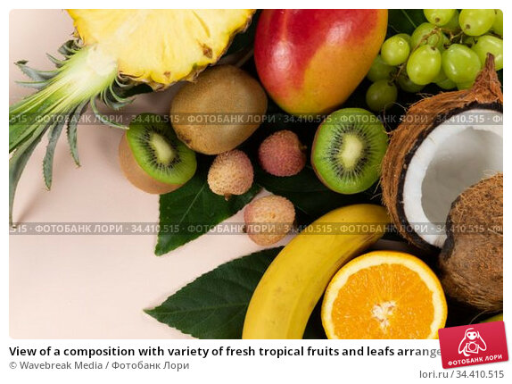 View of a composition with variety of fresh tropical fruits and leafs arranged on a pink surface. Стоковое фото, агентство Wavebreak Media / Фотобанк Лори
