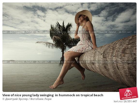 View of nice young lady swinging  in hummock on tropical beach, фото № 26551447, снято 21 августа 2017 г. (c) Дмитрий Эрслер / Фотобанк Лори