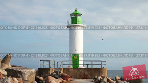 Купить «View to lighthouse, sea and stones in the morning in Ventspils, Latvia», видеоролик № 27819923, снято 9 сентября 2016 г. (c) Алексей Кузнецов / Фотобанк Лори