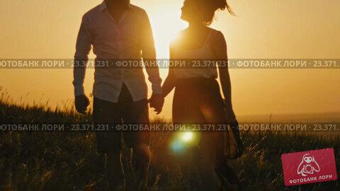 Купить «Влюблённая пара держится за руки на фоне заката», видеоролик № 23371231, снято 8 августа 2016 г. (c) Константин Шишкин / Фотобанк Лори