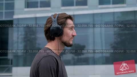 Walking Freelancer Man in the big urban city working with a laptop phone camera and listening music via headphones. Стоковое видео, видеограф Aleksejs Bergmanis / Фотобанк Лори