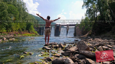 Water dam in the forest - a young man in shorts watching the view. Стоковое видео, видеограф Константин Шишкин / Фотобанк Лори