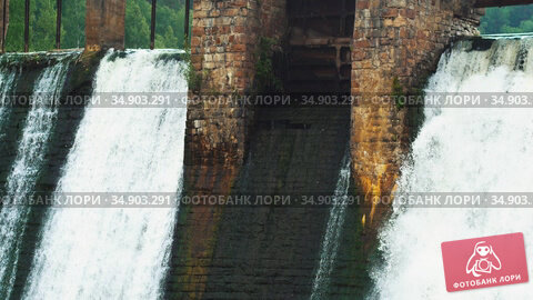 Water dam in the middle of the forest - water falls down under the bridge. Стоковое видео, видеограф Константин Шишкин / Фотобанк Лори