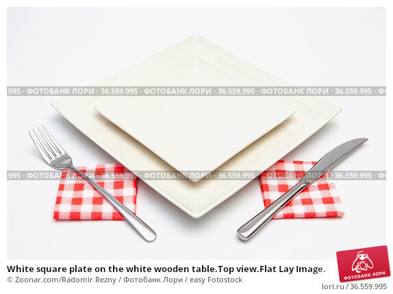 White square plate on the white wooden table.Top view.Flat Lay Image. Стоковое фото, фотограф Zoonar.com/Radomir Rezny / easy Fotostock / Фотобанк Лори