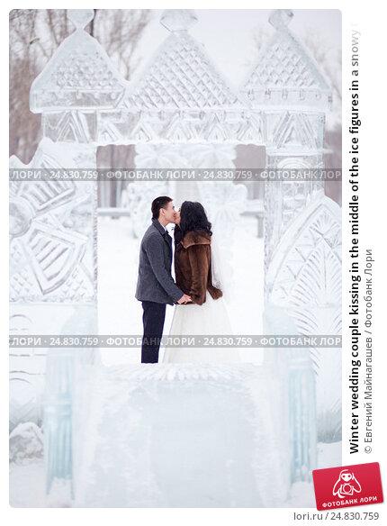 Купить «Winter wedding couple kissing in the middle of the ice figures in a snowy town, the bride in fur coat and white dress with veil, the groom wearing topcoat», фото № 24830759, снято 20 февраля 2016 г. (c) Евгений Майнагашев / Фотобанк Лори