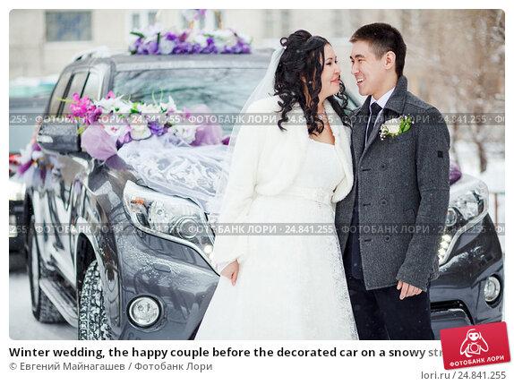 Купить «Winter wedding, the happy couple before the decorated car on a snowy street. Bride and groom look at each other.», фото № 24841255, снято 20 февраля 2016 г. (c) Евгений Майнагашев / Фотобанк Лори