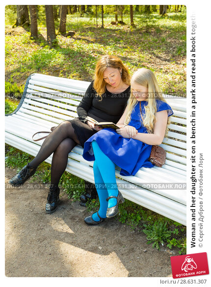 Купить «Woman and her daughter sit on a bench in a park and read a book together», фото № 28631307, снято 21 мая 2017 г. (c) Сергей Дубров / Фотобанк Лори