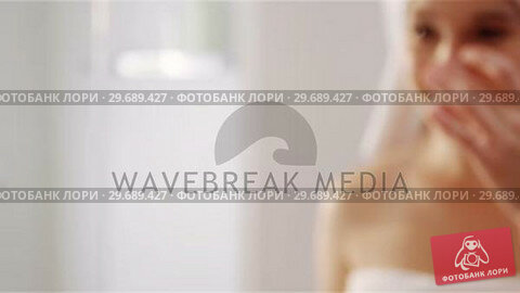 Купить «Woman applying moisturizer cream on her face in bathroom», видеоролик № 29689427, снято 26 августа 2016 г. (c) Wavebreak Media / Фотобанк Лори