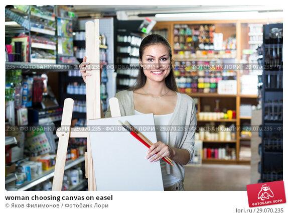 Купить «woman choosing canvas on easel», фото № 29070235, снято 16 января 2019 г. (c) Яков Филимонов / Фотобанк Лори