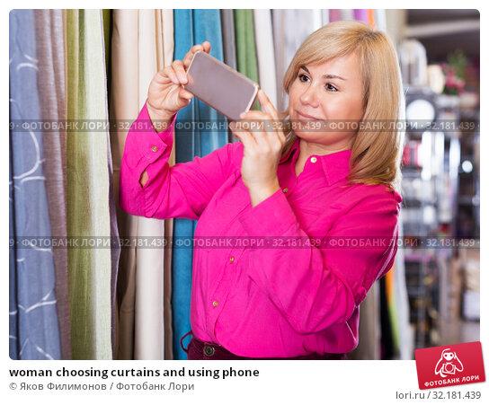 Купить «woman choosing curtains and using phone», фото № 32181439, снято 17 января 2018 г. (c) Яков Филимонов / Фотобанк Лори