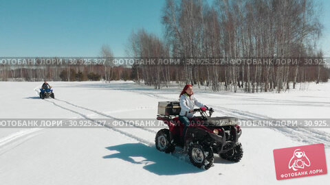 Купить «Woman driving ATV on the snow field man rides behind her», видеоролик № 30925327, снято 25 июня 2019 г. (c) Константин Шишкин / Фотобанк Лори