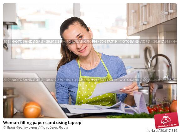 Купить «Woman filling papers and using laptop», фото № 30617319, снято 14 июля 2020 г. (c) Яков Филимонов / Фотобанк Лори