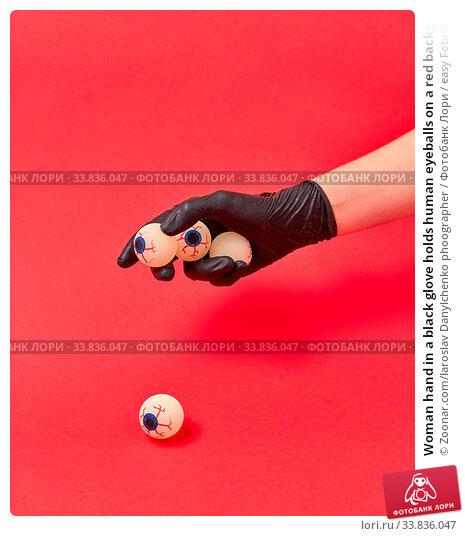 Купить «Woman hand in a black glove holds human eyeballs on a red background, copy space. Halloween simbol.», фото № 33836047, снято 30 мая 2020 г. (c) easy Fotostock / Фотобанк Лори