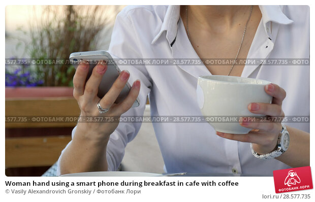 Купить «Woman hand using a smart phone during breakfast in cafe with coffee», фото № 28577735, снято 21 июня 2018 г. (c) Vasily Alexandrovich Gronskiy / Фотобанк Лори