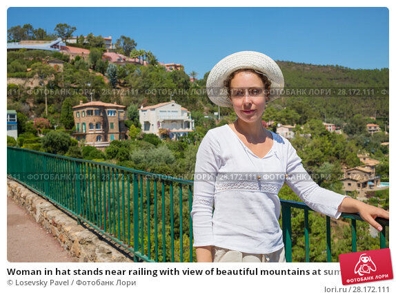 Купить «Woman in hat stands near railing with view of beautiful mountains at summer», фото № 28172111, снято 28 июля 2016 г. (c) Losevsky Pavel / Фотобанк Лори