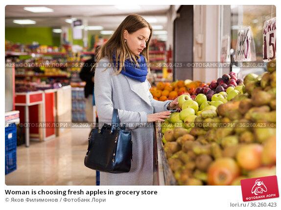 Woman is choosing fresh apples in grocery store. Стоковое фото, фотограф Яков Филимонов / Фотобанк Лори