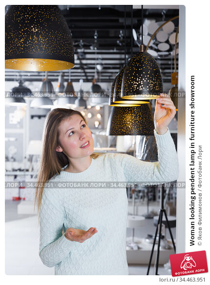 Woman looking pendent lamp in furniture showroom. Стоковое фото, фотограф Яков Филимонов / Фотобанк Лори