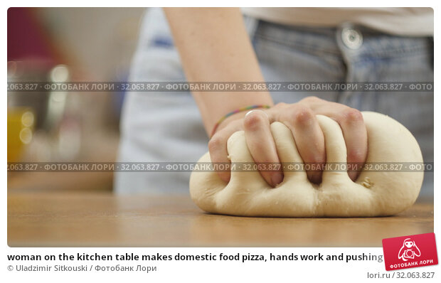 woman on the kitchen table makes domestic food pizza, hands work and pushing stir knead the dough, selective focus dolly shot. Стоковое фото, фотограф Uladzimir Sitkouski / Фотобанк Лори