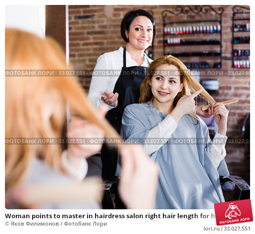 Woman points to master in hairdress salon right hair length for haircut. Стоковое фото, фотограф Яков Филимонов / Фотобанк Лори