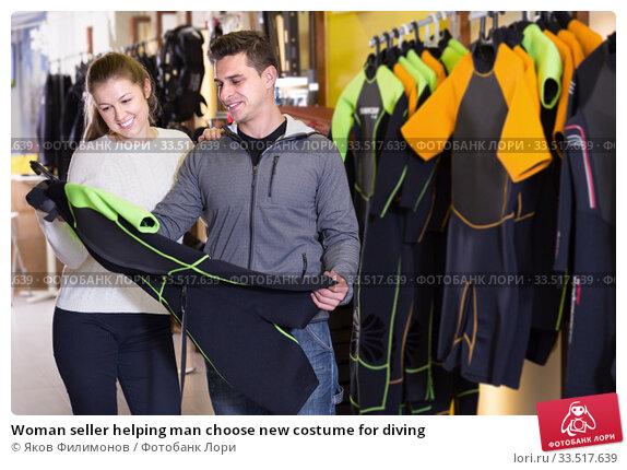 Woman seller helping man choose new costume for diving. Стоковое фото, фотограф Яков Филимонов / Фотобанк Лори