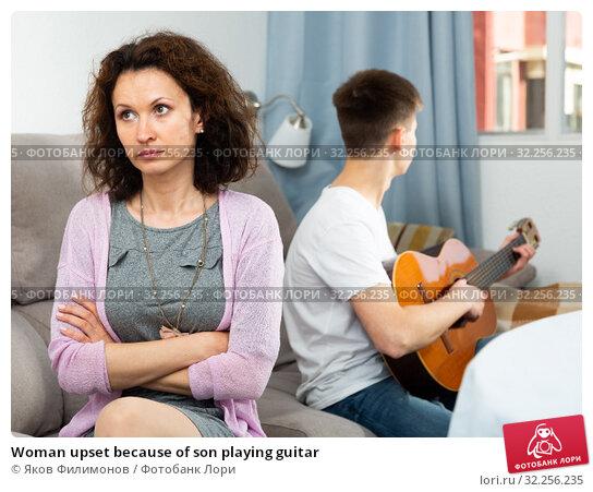 Woman upset because of son playing guitar. Стоковое фото, фотограф Яков Филимонов / Фотобанк Лори