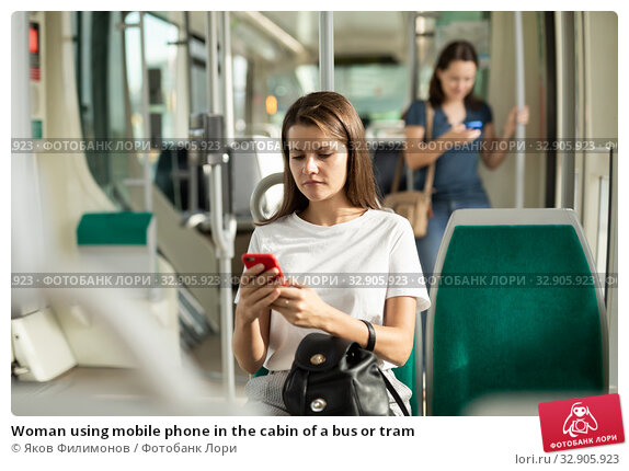 Woman using mobile phone in the cabin of a bus or tram. Стоковое фото, фотограф Яков Филимонов / Фотобанк Лори