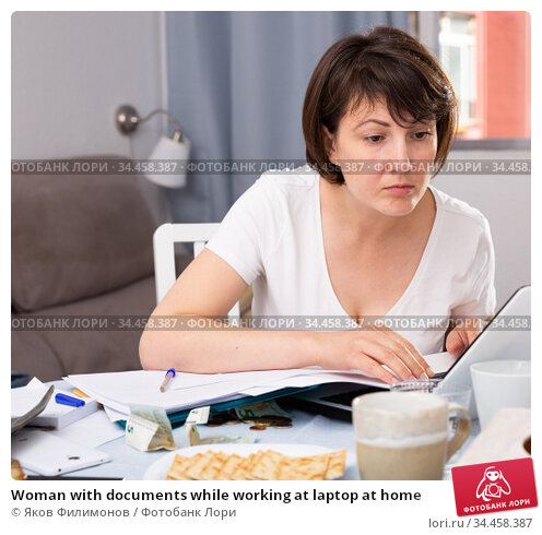 Woman with documents while working at laptop at home. Стоковое фото, фотограф Яков Филимонов / Фотобанк Лори