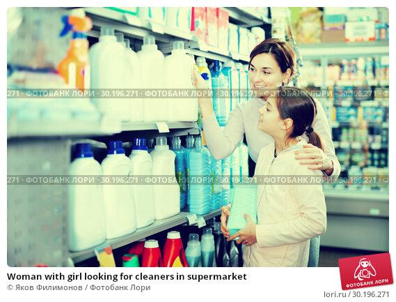 Купить «Woman with girl looking for cleaners in supermarket», фото № 30196271, снято 5 января 2017 г. (c) Яков Филимонов / Фотобанк Лори