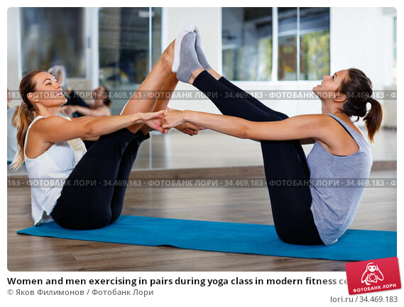 Women and men exercising in pairs during yoga class in modern fitness center. Стоковое фото, фотограф Яков Филимонов / Фотобанк Лори