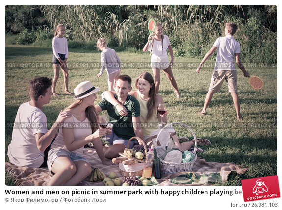 Купить «Women and men on picnic in summer park with happy children playing behind», фото № 26981103, снято 19 января 2018 г. (c) Яков Филимонов / Фотобанк Лори