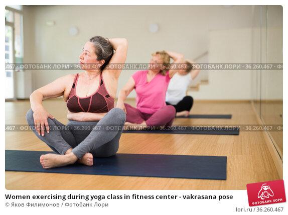 Women exercising during yoga class in fitness center - vakrasana pose. Стоковое фото, фотограф Яков Филимонов / Фотобанк Лори