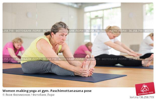 Women making yoga at gym. Paschimottanasana pose. Стоковое фото, фотограф Яков Филимонов / Фотобанк Лори