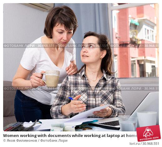 Купить «Women working with documents while working at laptop at home», фото № 30968551, снято 19 июля 2019 г. (c) Яков Филимонов / Фотобанк Лори