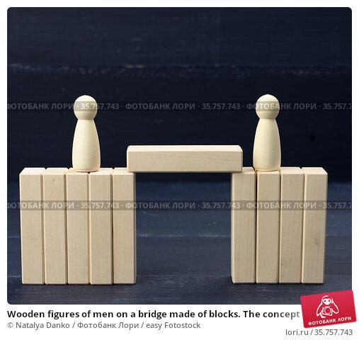 Wooden figures of men on a bridge made of blocks. The concept of a... Стоковое фото, фотограф Natalya Danko / easy Fotostock / Фотобанк Лори