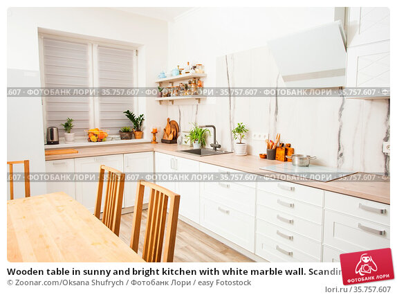 Wooden table in sunny and bright kitchen with white marble wall. Scandinavian... Стоковое фото, фотограф Zoonar.com/Oksana Shufrych / easy Fotostock / Фотобанк Лори