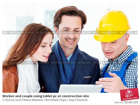 Worker and couple using tablet pc at construction site. Стоковое фото, фотограф Zoonar.com/Tatiana Badaeva / easy Fotostock / Фотобанк Лори