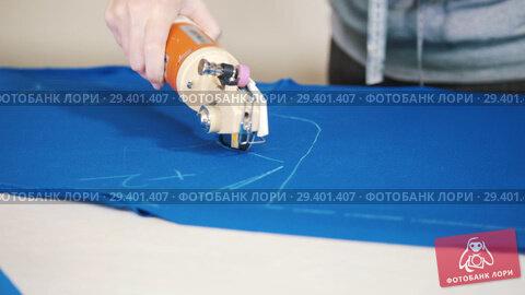 Купить «Worker at the factory cutting blue cloth using special instrument following the marks», видеоролик № 29401407, снято 24 января 2019 г. (c) Константин Шишкин / Фотобанк Лори