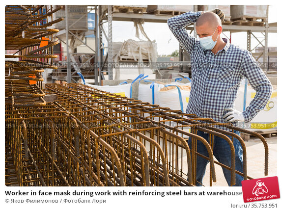 Worker in face mask during work with reinforcing steel bars at warehouse. Стоковое фото, фотограф Яков Филимонов / Фотобанк Лори