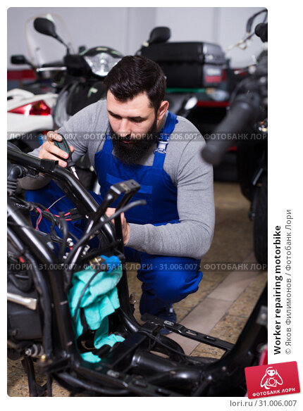 Купить «Worker repairing motorbike», фото № 31006007, снято 18 сентября 2019 г. (c) Яков Филимонов / Фотобанк Лори