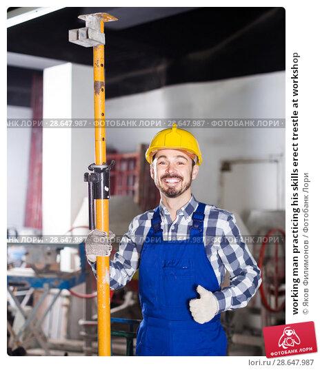 Купить «working man practicing his skills erect trestle at workshop», фото № 28647987, снято 17 января 2017 г. (c) Яков Филимонов / Фотобанк Лори