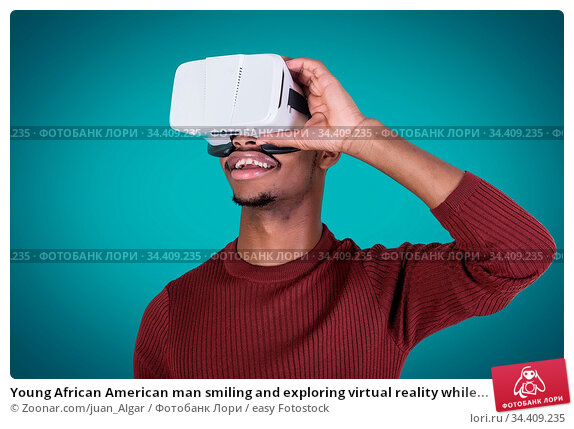Young African American man smiling and exploring virtual reality while... Стоковое фото, фотограф Zoonar.com/juan_Algar / easy Fotostock / Фотобанк Лори