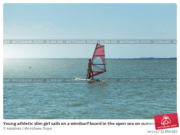 Young athletic slim girl sails on a windsurf board in the open sea on summer vacation at resort. Windsurfing. Стоковое фото, фотограф katalinks / Фотобанк Лори