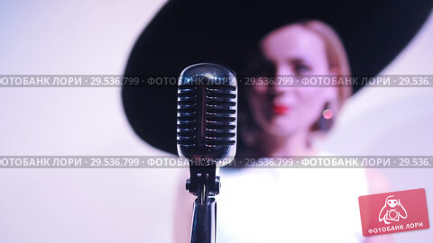 Купить «Young attractive woman standing near the mic on the background of a white wall in big hat. Mic in focus», видеоролик № 29536799, снято 10 декабря 2018 г. (c) Константин Шишкин / Фотобанк Лори
