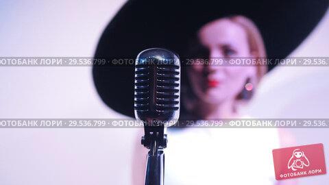Купить «Young attractive woman standing near the mic on the background of a white wall in big hat. Mic in focus», видеоролик № 29536799, снято 25 августа 2019 г. (c) Константин Шишкин / Фотобанк Лори