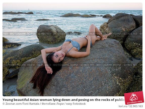 Young beautiful Asian woman lying down and posing on the rocks of public beach in Hua Hin Thailand. Стоковое фото, фотограф Zoonar.com/Toni Rantala / easy Fotostock / Фотобанк Лори
