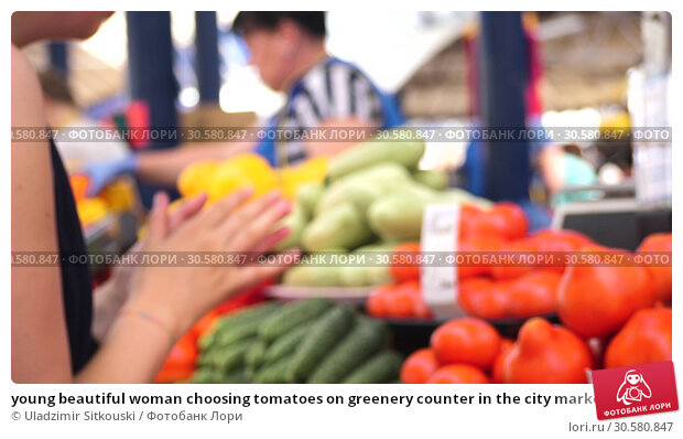 Купить «young beautiful woman choosing tomatoes on greenery counter in the city marketplace with an unrecognizable seller on the background, side view close up slow motion video in 4K», фото № 30580847, снято 20 апреля 2019 г. (c) Uladzimir Sitkouski / Фотобанк Лори