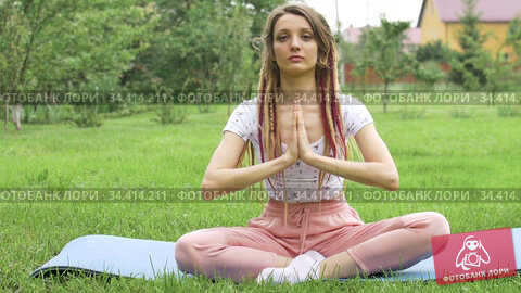 Young beautiful woman with dreadlocks is doing yoga sitting in lotus position outdoors during morning on green grass of her backyard. Стоковое видео, видеограф Ольга Балынская / Фотобанк Лори